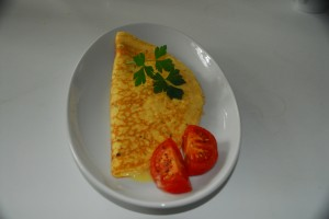 We make to order a range of Omelettes using locally sourced free range eggs and in this picture the filling is locally sourced Coastal mature Cheddar from Ford Farm with grilled vine tomato and fresh flat leaf parsley.